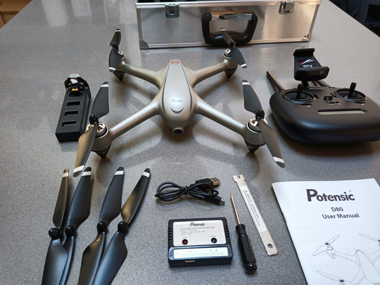 Le drone Potensic D80 est livré dans sa valise. Celle-ci comprends également batterie, chargeur et jeux d'hélices.